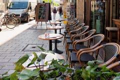 曼海姆,德国- 2017年4月10日:与咖啡馆的椅子infront的表街市为早餐或咖啡邀请 免版税库存图片