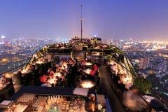 曼谷在从屋顶上面酒吧观看的夜之前用享受场面的许多游人 免版税库存图片