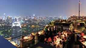 曼谷在从屋顶上面酒吧观看的夜之前用享受场面的许多游人 免版税库存照片