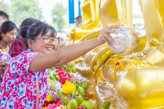 曼谷泰国- 2018年4月16日:Songkran节日,妇女用途倾吐对金黄菩萨雕象的水 Songkran节日是他 免版税库存照片