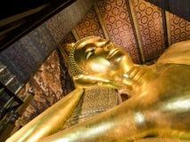 曼谷菩萨表面金子pho斜倚的雕象泰国wat 库存照片