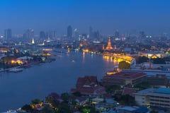 曼谷都市风景在能看到wat arun的微明的河边 免版税库存图片