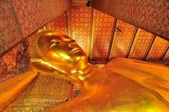 曼谷,泰国, 11:03上午 在的斜倚的菩萨雕象 库存照片