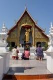 曼谷,泰国, 2018年3月06日:他们的kneew的未认出的人祈祷在金黄雕象前面的室外观点的 免版税库存照片