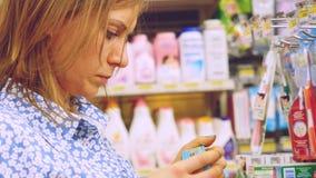 曼谷,泰国, 2015年11月22日 选择牙膏的少妇在商店 库存图片