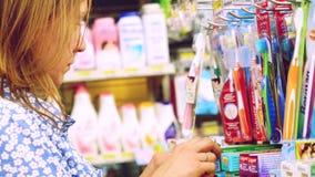 曼谷,泰国, 2015年11月22日 选择牙膏的少妇在商店 库存照片