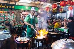 曼谷,泰国- 2019年3月:烹调海鲜的人在中国夜市农贸市场餐馆 库存图片