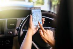 曼谷,泰国- 2017年11月12日, :使用手机的妇女的手计划有谷歌地图的一条路线在屏幕在汽车 免版税库存照片
