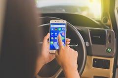 曼谷,泰国- 2017年11月12日, :使用有社会媒介象的妇女的手手机在屏幕上的在汽车 免版税库存照片