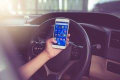 曼谷,泰国- 2017年11月12日, :使用有社会媒介象的妇女的手手机在屏幕上的在汽车 库存图片