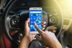 曼谷,泰国- 2017年11月12日, :使用有社会媒介象的妇女的手手机在屏幕上的在汽车 免版税库存图片