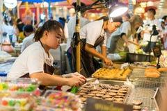 曼谷,泰国- 2017年8月5日:做新鲜的泰国点心的泰国女性糖果供营商,它的名字是`剧痛美国兵`椰子薄煎饼 库存照片