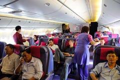 曼谷,泰国- 2010年10月29日:在飞行中泰航波音777-300服务在企业classRoyal丝绸类客舱的 免版税库存照片