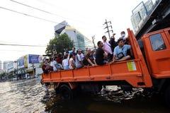 曼谷,泰国- 2011年11月9日:大卡车在与最重的涌来和雨的冲击以后运载了水灾受害者在20年 库存照片