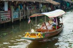 曼谷,泰国- 2018年2月11日:游人喜欢旅行乘在小伙子Mayom运河的旅游长尾巴小船 免版税库存图片