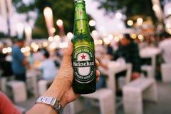 曼谷,泰国- 2018年12月31日:被递的瓶在被弄脏的五颜六色的轻的bokeh的冷的海涅肯啤酒在背景中, 免版税库存图片
