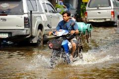 曼谷,泰国- 2011年11月5日:送货人在暴雨以后驾驶在一条被充斥的街道上的一辆摩托车 免版税库存图片