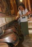 曼谷,泰国- 2014年4月29日 作为提供的泰国妇女储蓄硬币在一名修士的一个碗斜倚的寺庙的金黄 免版税库存图片
