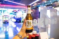 曼谷,泰国- 2018年4月14日:被递的瓶在被弄脏的五颜六色的轻的bokeh的冷的singha啤酒在reatautant,有选择性 库存图片