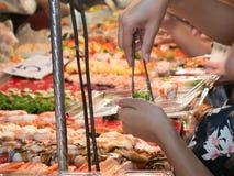 曼谷,泰国- 2016年11月14日:妇女递买寿司在Loy Kratong节日曼谷,泰国的夜市场上 免版税库存照片