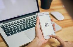 曼谷,泰国- 2017年8月23日:拿着电话的妇女在网上显示Seven-Eleven app屏幕 Seven-Eleven是最大的conv 库存照片