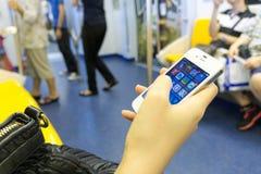 曼谷,泰国- 2014年10月15日:未认出的妇女使用在天空火车的手机 免版税库存图片