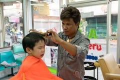 曼谷,泰国- 2015年1月17日:男孩理发和他不 免版税库存照片