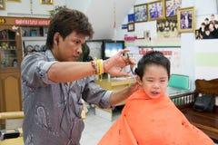 曼谷,泰国- 2015年1月17日:男孩理发和他不 免版税库存图片