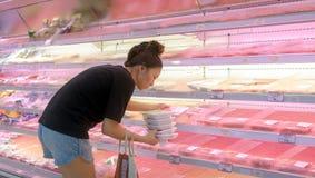 曼谷,泰国- 3月24:新鲜的被包装的肉的未认出的顾客商店在Foodland超级市场的肉部分  库存图片