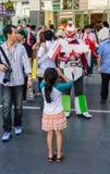 女孩拍摄一Gundam cosplayer。 免版税库存图片