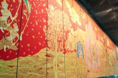 曼谷- 2010年:在红色的佛教在木盘区的绘画和金子 库存照片