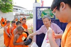 曼谷- 2014年4月:一位未认出的佛教徒放食物奉献物入一个佛教新手的碗在2014年4月20日在曼谷, Thail 库存图片