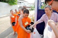 曼谷- 2014年4月:一位未认出的佛教徒放食物奉献物入一个佛教新手的碗在2014年4月20日在曼谷, Thail 库存照片