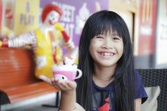 曼谷- 10月17 :微笑的亚裔女孩,在软的焦点,在麦克唐纳10月的` s餐馆显示了她愉快的膳食食物和玩具 库存照片