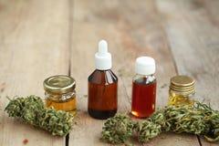 替代医学医药大麻绿色叶子与萃取物的在一张木桌上上油 免版税库存照片