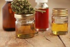 替代医学医药大麻绿色叶子与萃取物的在一张木桌上上油 图库摄影