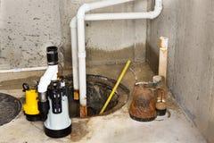 替换在地下室的老井底水窝水泵 免版税库存图片