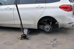 替换在汽车的轮子,起重器拿着在被上升的位置的身体 免版税库存图片