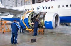 替换在飞机的引擎,工作者 航空器概念维护  免版税库存图片