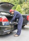 替换对备用轮胎的技工在汽车的后面 免版税库存照片