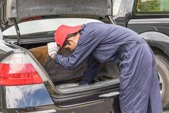 替换对备用轮胎的技工在汽车的后面 库存照片