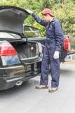 替换对备用轮胎的技工在汽车的后面 图库摄影
