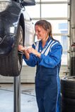 替换车轮胎的女性技工 免版税库存照片