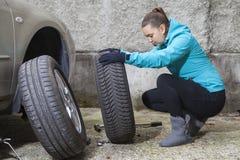 替换轮胎的年轻微笑的妇女司机 图库摄影