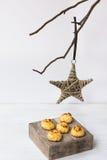 最低纲领派圣诞节和新年装饰,藤条星垂悬在一个干燥树枝的,在木箱子的椰子蛋白杏仁饼干 库存照片