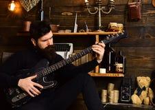 最佳的周末 人有胡子的音乐家喜欢与低音吉他,木背景 有胡子的人举行黑色 免版税库存照片