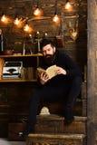 最佳的周末 有胡子的人拿着旧书并且读了 放松舒适温暖的大气的人,当有胡子时读书的人 库存照片