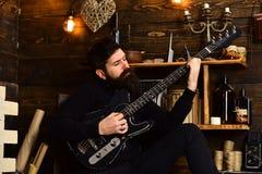最佳的周末 有胡子的人拿着黑电吉他 人有胡子的音乐家喜欢与低音吉他,木 免版税库存图片