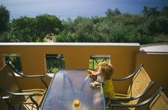 最佳的夏日 在大阳台的早餐 在海附近的公寓 希腊早晨 孩子的食物 免版税库存照片