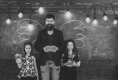 最佳的教师 老师和女孩学生在教室,在背景的黑板 孩子和老师有拉长的由白垩 免版税库存图片
